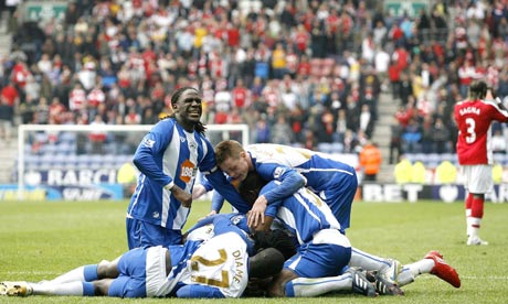 Charles N'Zogbia is mobbed by teammates after scoring Wigan's winner against Arsenal