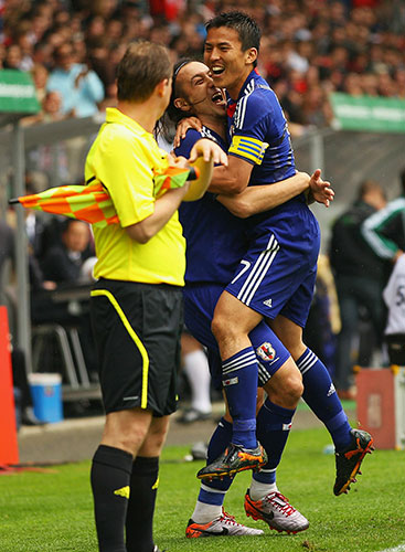 Marcus Tulio Tanaka celebrates with Makoto Hasebe after scoring the opener against England